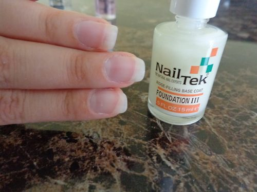 finger nails with polish beside a bottle of nail tek foundation III