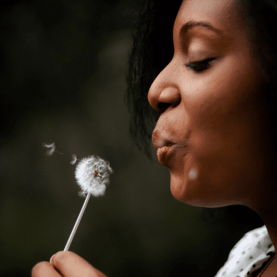 black woman blowing dandelion featured
